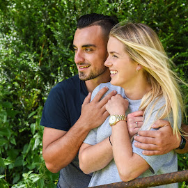 Smiling man holding blonde girlfriend behind gate by Nick Dale - People Couples ( countryside, exterior, rusty, long, romance, pretty, hispanic, iron, caucasian, love, farm, latino, girl, rusting, t-shirt, woman, attractive, grey, couple, hair, smiling, man, fields, affection, beautiful, white, woods, young, rural, gate, blonde, bushes, dress, outdoors, bearded, beard, trees, handsome, good-looking )