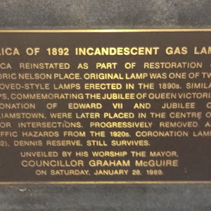 Plaque reads:'Replica of 1892 Incandescent Gas LampReplica reinstated as part of restoration of historic Nelson Place. Original lamp was one of two improved-style lamps erected in the 1890's. Similar ...