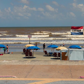 Fun at the Beach by Bonnie Davidson - Public Holidays July 4th ( clouds, water, sand, white, ocean, yellow, beach, landscape, people, city, holiday, galveston island, sky, umbrellas, nature, blue, beige, gulf of mexico )
