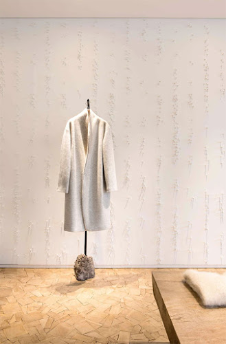 patchwork wood floor with white pins wall white coat on free standing rack pas de calais store in paris photo by Helene Hilaire