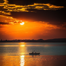 Sunset by Ovidiu Domsa - Landscapes Waterscapes ( water, clouds, waterscape, boats, sport, canoe, lake, boat, sunlight, people, sun, fire, red, sky, color, sunset, sunsets, landscape;, landscapes )