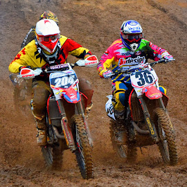 Duelling by Marco Bertamé - Sports & Fitness Motorsports ( rainy, yellow, duelling, race, uphill, motocycle, red, mud, bike, motocross, clumps, pink, accelerating, competition )