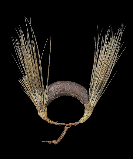 Barkcloth was associated with the divine power of the gods in eastern Polynesia, where abstract god images might be covered or wrapped in barkcloth. Items of adornment often combined materials and colours connected with gods and ancestors, magnifying the status of the wearer. This headdress combines tail feathers from the tropic bird with black barkcloth, both potent elements of wrapped god images from the Cook Islands. As part of a headdress for festive occasions, these materials would have contributed to a singularly impressive costume.