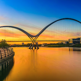 Infinity Bridge at sunset In Stockton-on-Tees, UK by Nuttawut Uttamaharach - Buildings & Architecture Bridges & Suspended Structures ( illuminated, crossing, reflection, moon, europe, warm, bowstring, foot, teeside, architecture, north, travel, landscape, across, infinity, city, lights, stockton, ีuk, england, march, sky, pedestrian, kingdom, full, dark, east, water, clouds, tees, united, building, stockton-on-tees, purple, morning, dusk, landmark, sunset, arches, night, bridge, sunrise, river )