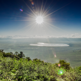 View of Ngorongoro Crater from the Rim by Jacques Jacobsz - Landscapes Travel ( ecosystem, sanctuary, plants, wildlife, beauty, protect, landscape, tanzania, sun, distance, conserve, sky, nature, conservation, magadi, bush, ecology, africa, ngorongoro, top, water, protection, clouds, green, lake, rim, crater, habitat, floor, blue, view, flares, natural )