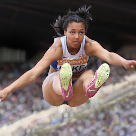She flies through the air with the greatest of ease.  by Ron Russell - Sports & Fitness Running ( athletics, jumping, crowds, longjumper, sport, people, running, championships, flight, winning, distance, female, stadium, competition )