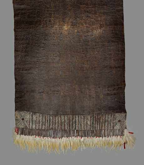 As a valuable trade item this finely decorated barkcloth was used within ceremonial exchanges, such as marriage payments and chiefly rituals. It is painted with turmeric, red and brown clay pigments, and sealed with black pigment mixed from ash, giving it a shiny varnished appearance. The fringe of feathers and imported red cloth enhances its value further. The band of painted geometric decoration along the border is similar to barkcloth designs from neighbouring Polynesian islands from which this community had presumably migrated.