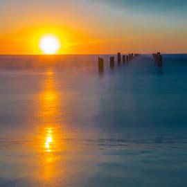 A glowing sunset over the pier by Ilan Abiri - Landscapes Sunsets & Sunrises ( colors, sunset, sea, long exposure, ocean, beach, landscape, skies, sun )
