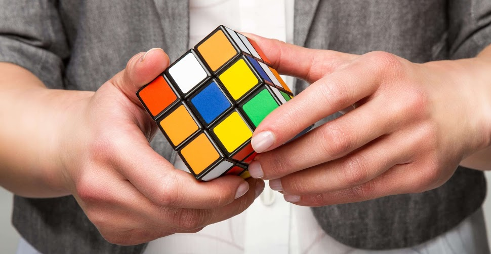 a person's hands playing with a rubik's cube