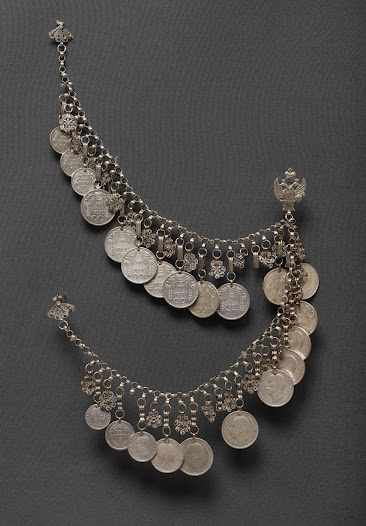 <b>A coin chain (nizalka)</b> Early 1900s  A woman's coin chain, a 'nizalka'. The coins are Bulgarian and Serbian, dated between 1882 and 1938, and are suspended together with filigree amulets from a heavy silver chain, and secured onto the upper sash by three decorative hooks, the central one having the Serbian royal coat of arms and the two outer made of silver filigree work. Worn at the wedding and subsequently on festive occasions.