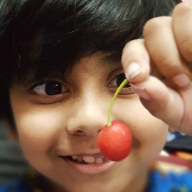 Baby with a cherry by Rickta Dutta - Babies & Children Child Portraits ( cherry, lovely, foods, cherries, happy, cooking, portrait, india, kids )
