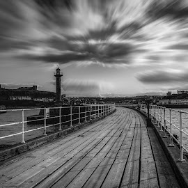 Black and white image of Whitby pier at the harbour entrance at  by Nuttawut Uttamaharach - Buildings & Architecture Bridges & Suspended Structures ( calm, exposure, cliffs, ocean, north, architecture, seaside, long, landscape, coast, attraction, tranquil, england, kingdom, yorkshire, gorgeous, pier, evening, light, black, water, united, uk, beautiful, twilight, white, sea, tourism, whitby, seascape, scenic, postcard, coastal, seagull, dawn, sunset, outdoor, ripple, tranquility, sunrise )