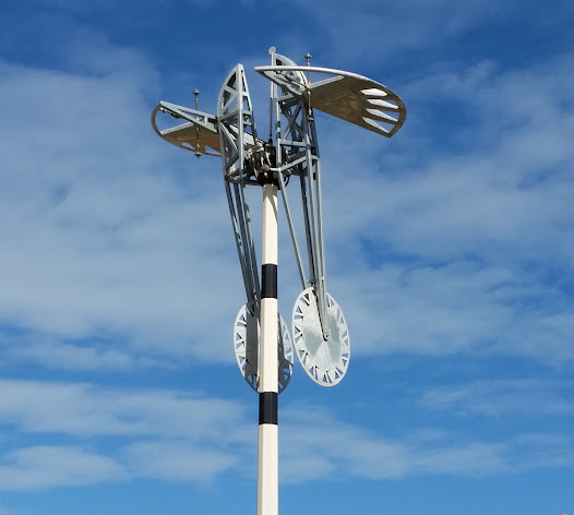 Adjacent to the Oxnard Airport in California, this sculpture's kinetic design illustrates its aviation theme by simulating aircraft aileron movement.