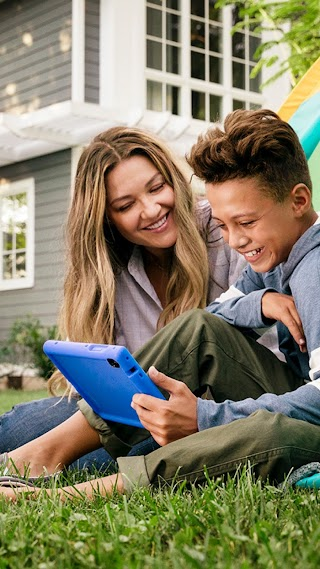 Mother and son both using a tablet while camping in their backyard.