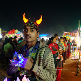 A vendor of the fair by Mihir Ranjan - People Street & Candids ( a vendor selling toys in the fair, vendor in the fair, street vendor, selling toys, a vendor of the fair, street scene, vendor of toys )