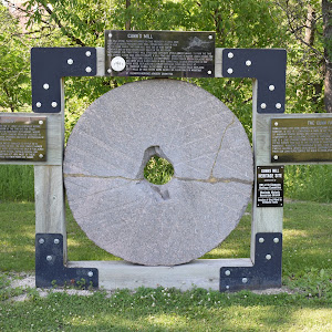 Three plaques in one! This mill stone surrounded by plaques stands next to the Half Moon Drive In near Lockport, Manitoba. Here is the transcription of the plaques, from left to right: PLAQUE 1:RIVER ...