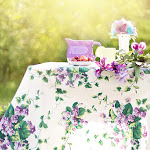 Table with floral tablecloth, flowers and jug