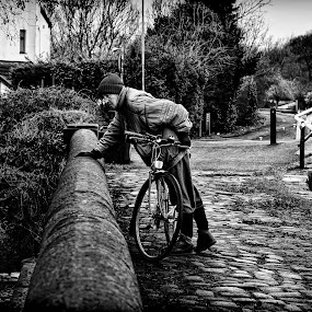 Curiosity by Jon Hunter - People Street & Candids ( cobbles, water, black and white, street, male, candid, canal, bicycle )