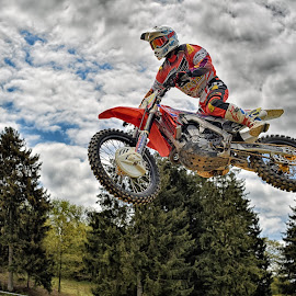 Crazy Red Devil ! by Marco Bertamé - Sports & Fitness Motorsports ( clouds, speed, green, forest, number, race, jump, noise, 2, flying, red, motocross, blue, cloudy, grey )