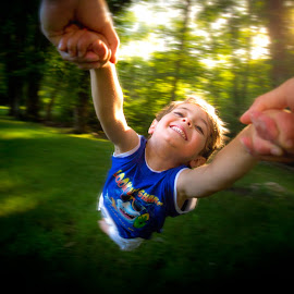 Flying by Mike DeMicco - Babies & Children Child Portraits ( children, happiness, fun, playing, love, child, flying, silly, spinning, backlight, happy, light, boy, outside )