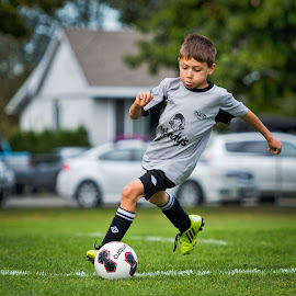 Controlling the Ball by Garry Dosa - Sports & Fitness Soccer/Association football ( tournament, ball, outdoors, boys, sports, children, grey, game, people, running, soccer )