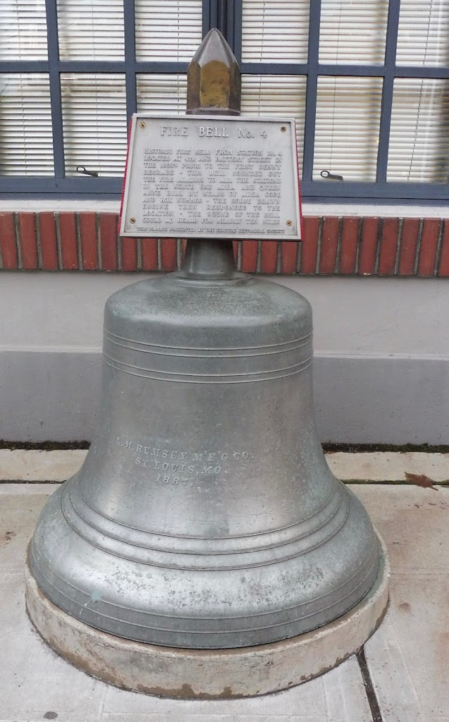 The plaque is on top of a bell; its text reads: