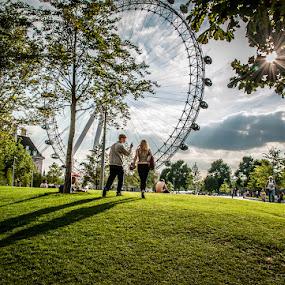 The London Eye by Matt Cooper - City,  Street & Park  City Parks ( ray, walking, wheel, grass, green, people, sun, waterloo, city, south bank, tree, london, metal, shadow, branch, cloud, boy, eye )