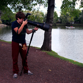 Photographer in action by Cristobal Garciaferro Rubio - Professional People Technology Workers ( lagoon, photographer, lake, boy )