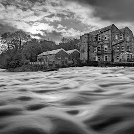 By The River by Darrell Evans - Black & White Buildings & Architecture ( water, clouds, building, old, wier, black & white, river aire aire, stone, flow, sky, yorkshire, outdoor, trees, rapids )