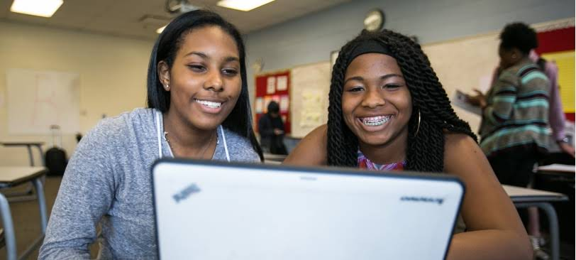 Two Girls taking a look a screen and smiling