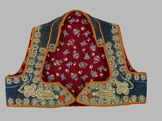 <b>Serbian woman's waistcoat (jelek)</b> Early 1900s  This waistcoat would have been worn over a white blouse with Ottoman-style gathered silk trousers. This waistcoat is made of cotton velvet cloth decorated back and front with couched embroidery in gold- and silver coloured metal-wrapped thread, metal sequins and tiny red plastic beads. The printed cotton lining dates from the 1920s or 1930s.