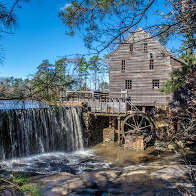 The Mill by Thomas Shaw - Buildings & Architecture Public & Historical ( clouds, wheel, wood, waterfall, windows, historic yates mill, raleigh, historic, north carolina, sky, yates mill, trees, pine trees, pine, rocks )