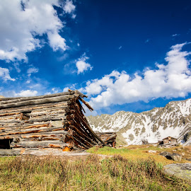 Mayflower Gulch by Mike Thompson - Landscapes Mountains & Hills ( clouds, building, mountain, wood, green, beautiful, sun, daytime, mountains, wooden, sky, blue, snow, day )