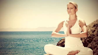 Beautiful-positiveblond-girl-clothing-in-white-sit-at-the-seaside-on-the-rock-and-meditating-in-yoga-pose