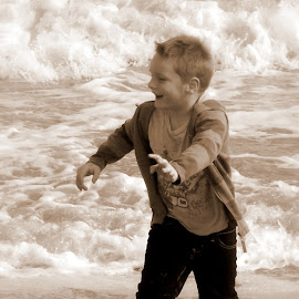 Childish Joy by Adriette Benade - Babies & Children Children Candids ( water, sepia, monochrome, child portrait, child photography, sea, monotone, sea shore, child, monochromatic, water play, child candid, boy, mono )