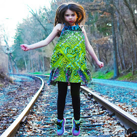 In Action by Tiffany Serijna - Babies & Children Child Portraits ( dreamy, jumping, dream, colorful, green, raelyn, little, candid, fun, tracks, portrait, jump, playing, child, girl, rail road, rae, outside )