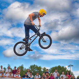 by Marco Bertamé - Sports & Fitness Other Sports ( clouds, wheel, twou, spectators, dow, yellow, stunt, helmet, jump, flying, blue, cloudy, air, grey, high )