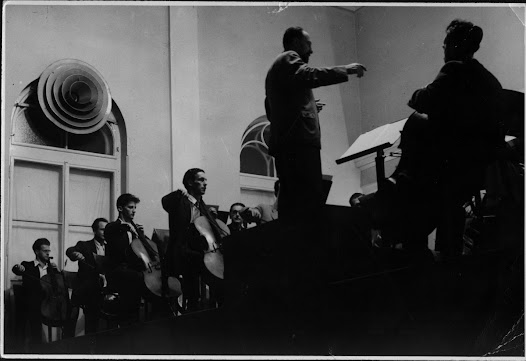 Matz conducts the first performance of his own composition, the Suite in F Major for Violoncello Ensemble, in 1950.  Antonio Janigro (on Matz's left) plays in the cello orchestra.
