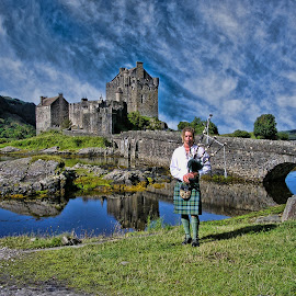 Eilan Donan castle Scotland by Gianluca Presto - People Musicians & Entertainers ( scotland, reflection, mask, architecture, people, pipe, historic, highland, playing, ancient, sky, tradition, cloudy, man, water, music, clouds, bagpipe, play, scottish, lake, traditional, highlander, highlands, piper, legend, costume, castle, bridge, boy )