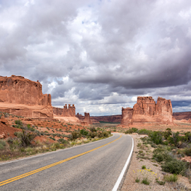 Road through Arches by Phyllis Plotkin - Landscapes Caves & Formations ( clouds, rock formations, road, landscape )