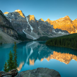 Sunrise at Moraine Lake, Banff National Park by Kenneth Lui - Landscapes Sunsets & Sunrises ( turquoise water, quiet morning, reflection, snow capped peaks, blue water, kayak, landscape, moraine lake, blue sky, nature, banff national park, gold, water, orange, wild, near lake louie, sunrise lighting, park, canada, alberta, green, forest, lake, golden hours, calm water, turquoise color, wilderness, blue color, blue, outdoor, golden orange, trees, mountain ranges, earth, sunrise, still water, golden, peaks, soft glow )
