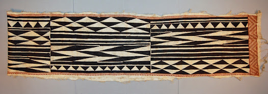 For Fijian chiefs, wearing barkcloth <i>masi</i> was a magnificent show of status. Long, narrow cloths like these were often wrapped or looped around the body in such a way that the whole garment could be released with one flourish, and then presented to visitors at a ceremonial occasion.  A decorated cloth like this would have been presented of worn as wrapping for special occasions. Barkcloth garments enhanced the visual impact of warriors, who paraded in their finery at ceremonies and before their opponents.  Bold black and white designs using triangles and lozenge shapes are characteristic of barkcloth made in the Cakaudrove province, which includes the island of Taveuni and the southeastern coast of Vanua Levu.