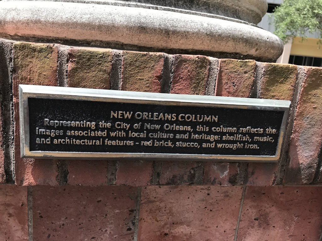 Representing the City of New Orleans, this column reflects the images associated with local culture and heritage: shellfish, music, and architectural features - red brick, stucco and wrought iron.