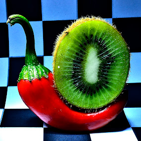 chili kiwi embrace by Angelo Jadulco - Food & Drink Fruits & Vegetables ( kiw, fruit, red, spice, red chili, chekered, green and red, vegetable, chili )