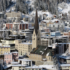 Davos, Graubünden, Switzerland by Serguei Ouklonski - City,  Street & Park  Vistas ( building, mountain, church, colors, no person, tourism, cityscape, travel, architecture, graubünden, panorama, city, roof, urban, sight, building exterior, winter, no people, outdoors, snow, switzerland, high, town, day, built structure, panoramic )