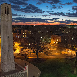 Tower at sunset by Thomas Shaw - Buildings & Architecture Statues & Monuments ( clouds, world war 2 memorial, orange, university, memorial, grass, green, brick, bell tower, yellow, raleigh, north carolina, north carolina state university, bell, ncsu, tower, world war 2 monument, cars, trees, streets, monument, roads, campus )