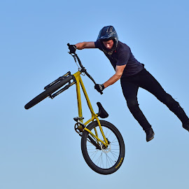 Playing With His Bicycle by Marco Bertamé - Sports & Fitness Other Sports ( sky, blue, air, yellow, acrobatic, jump, bicycle )