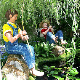 Huck Finn and Tom Sawyer by Dee Haun - City,  Street & Park  City Parks ( bellagio, flower sculpture, colorful, tom sawyer, flower arrangements, 040601p021e1, fishing, flowers, pond, huck finn,  )