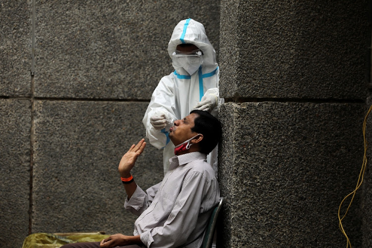 A healthcare worker wearing personal protective equipment (PPE) collects a swab sample from a man amidst the spread of the coronavirus at a testing center in New Delhi, India.