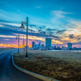 Glass City Sunset by Dazz Lee Briggs - City,  Street & Park  Skylines ( skyline, streetscape, street lamps, street, landscape, urban landscape, city, cloud formations, colorful sky, toledo, ohio, road to nowhere, sunset, toledo ohio, downtown, builidings )